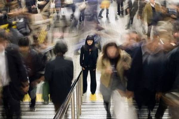 Girl standing amongst the blur of people passing by in a busy city