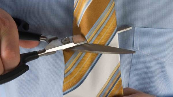 Someone cutting their office tie in half